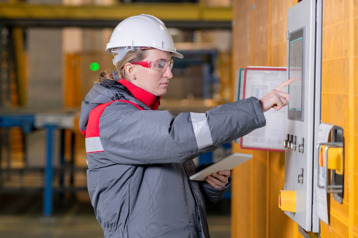 Das Bild zeigt eine Frau vor einem Schaltkasten