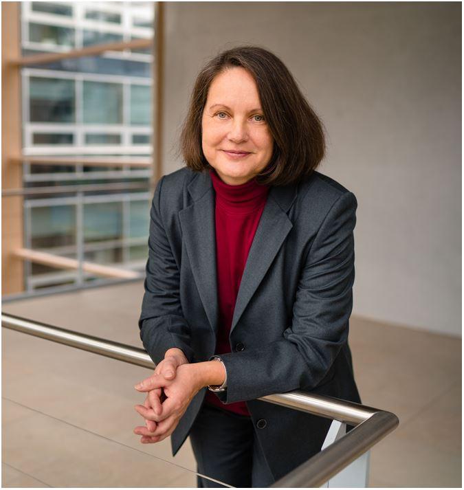 Die Expertin für Digitalisierung und Informatik Prof. Dr. Weisbecker lehnt an einem Geländer und lächelt.