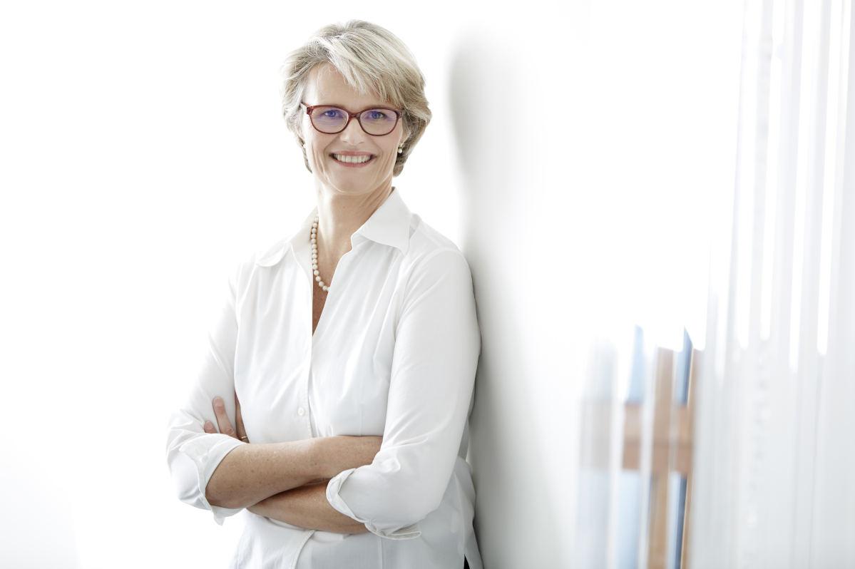 Bundesforschungsministerin Anja Karliczek lehnt in einer weißen Bluse an der Wand und lächelt in die Kamera.