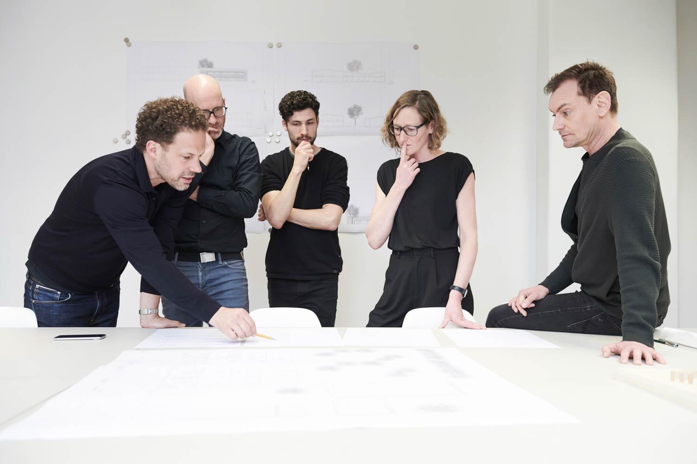 Das Foto zeigt Liza Heilmeyer und ihre Kollegen, wie sie beratend über Plänen stehen.