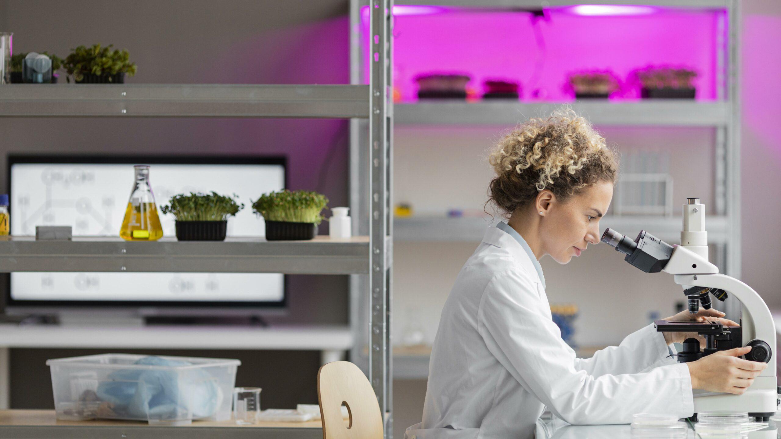 Zum Tag der Frauen in der Wissenschaft ist hier ein Symbolbild einer Wissenschaftlerin im Laborkittel am Mikroskop abgebildet.