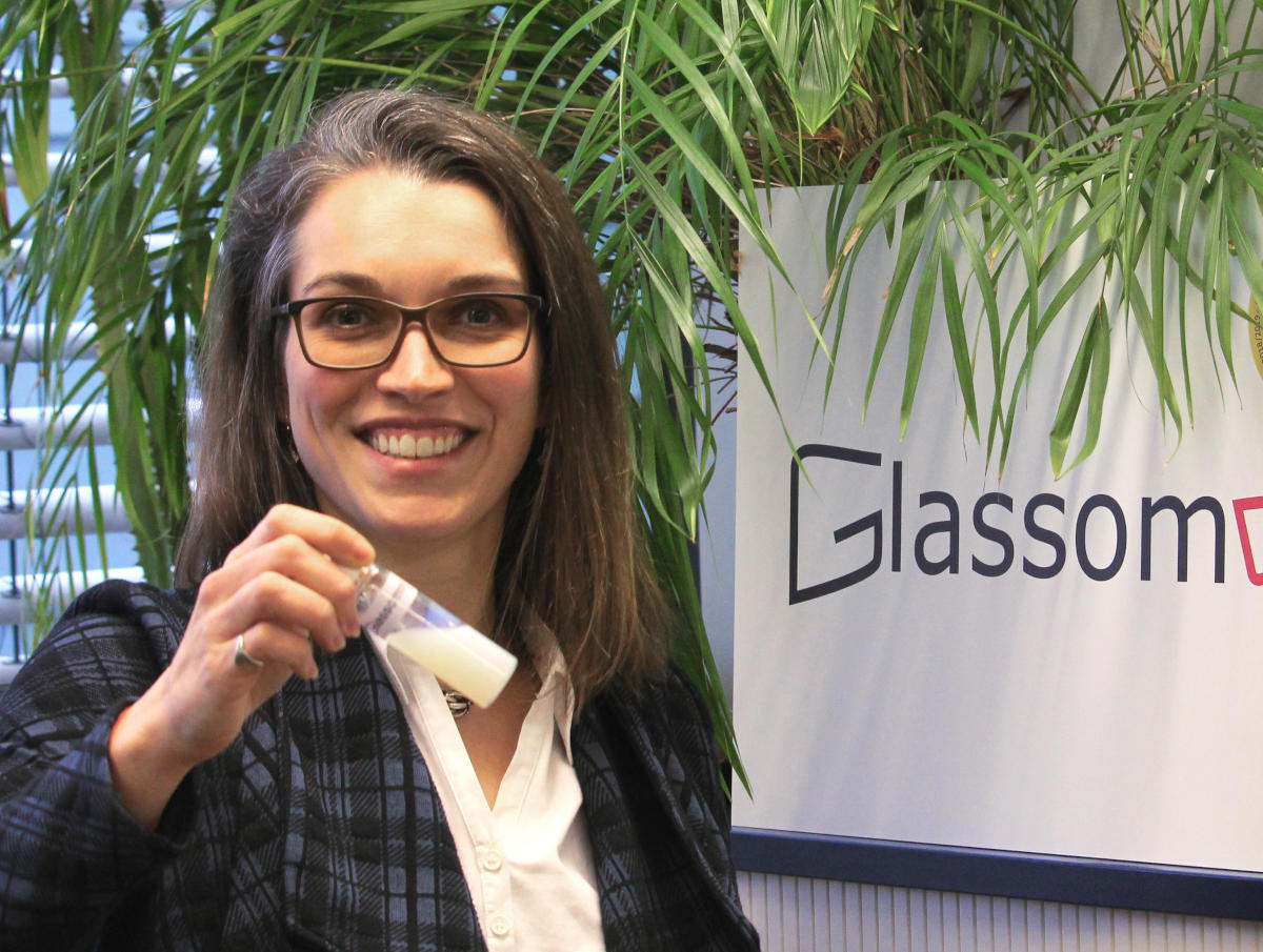 Das Bild zeigt Glassomer CEO Dr. Dorothea Helmer vor einer Pflanze, wie sie ein Reagenzglas mit einer milchigen Flüssigkeit in die Kamera hält: flüssiges Glas.