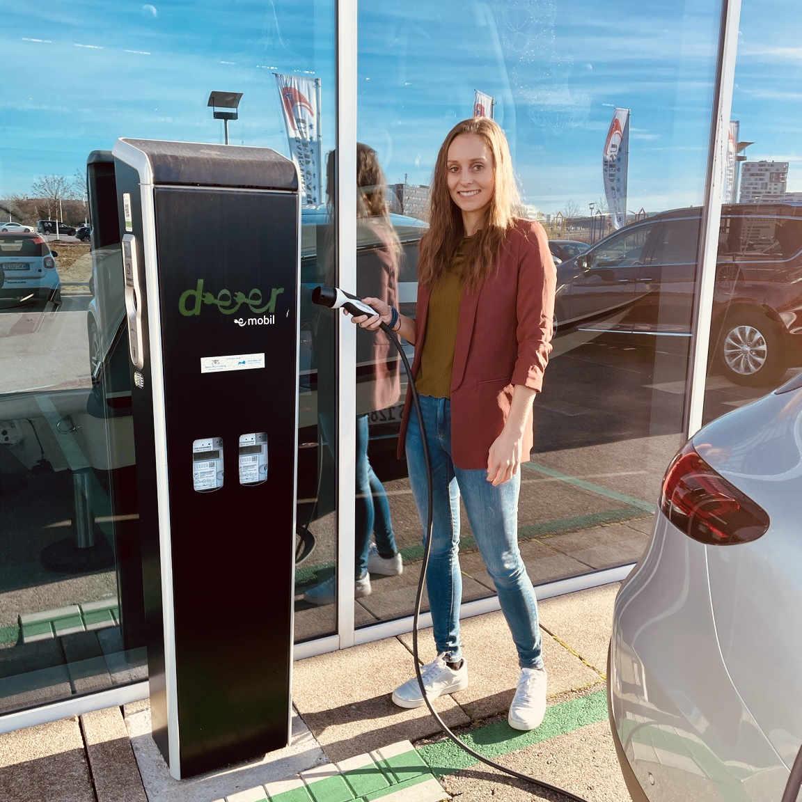 Rebecca steht an einer E-Ladesäule und beweist ihren Sinn für die Mobilität der Zukunft.