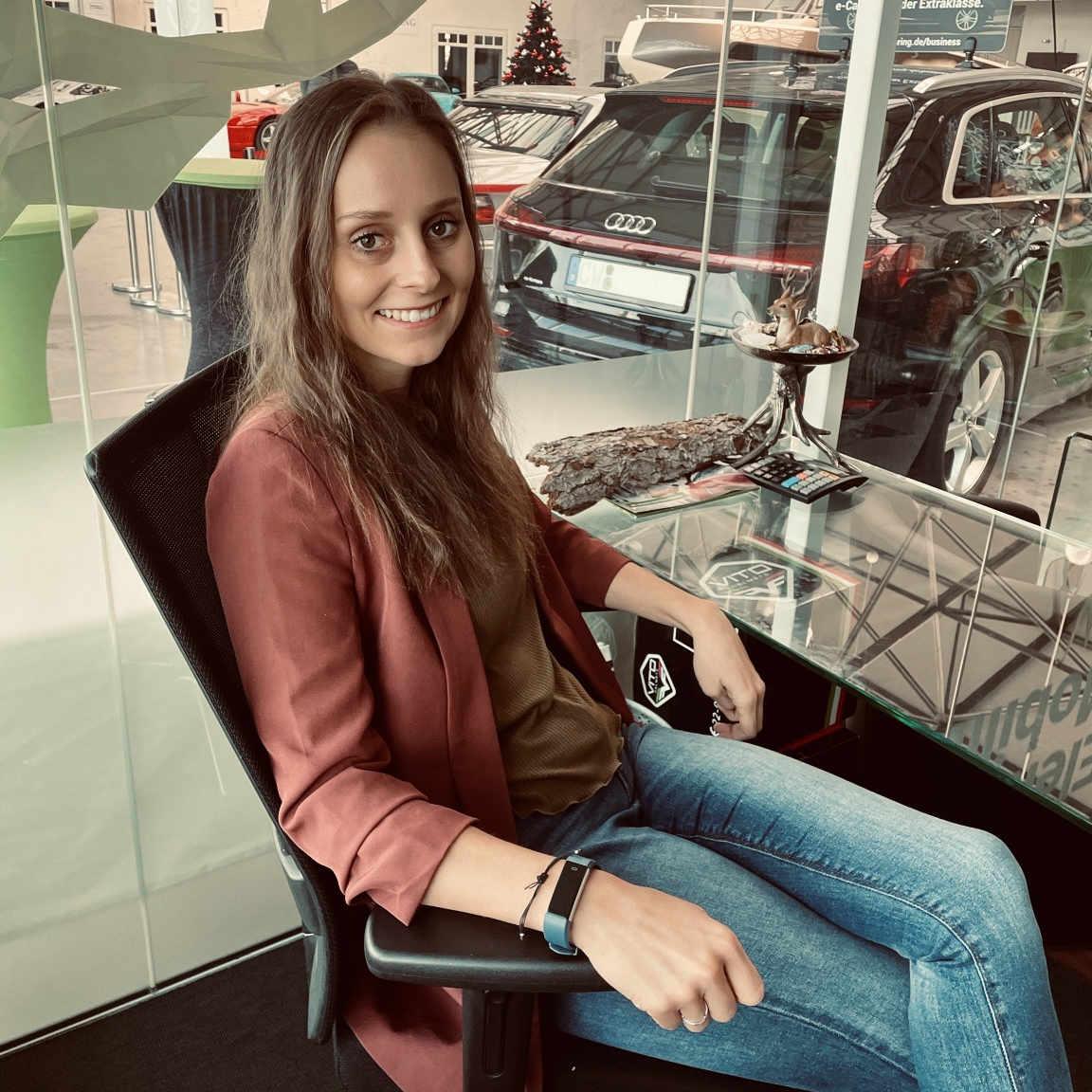 Rebecca sitzt am Schreibtisch im Büro, im Hintergrund sind E-Autos zu sehen - immer im EInsatz für die Mobilität der Zukunft.