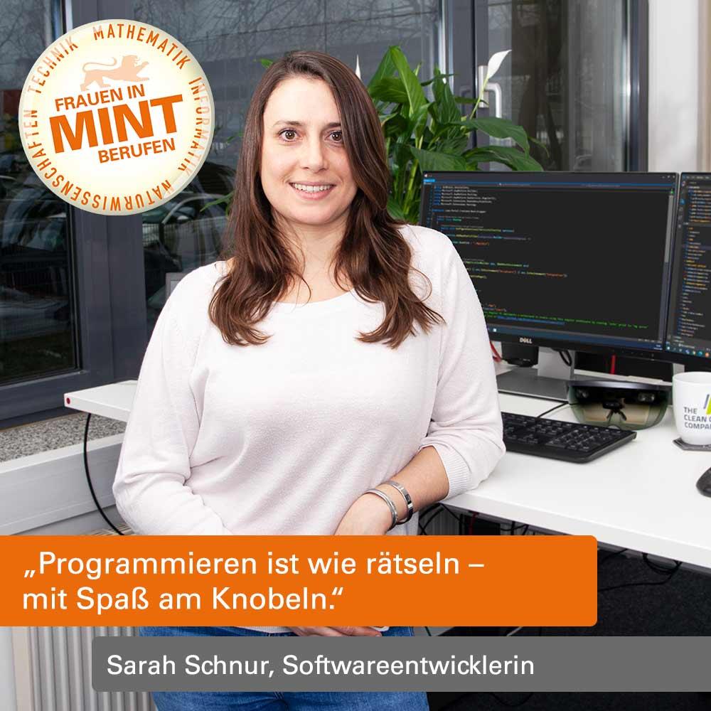 Das Bild zeigt die Softwareentwicklerin Sarah Schnur an ihrem Arbeitsplatz vor einem Rechner stehend.
