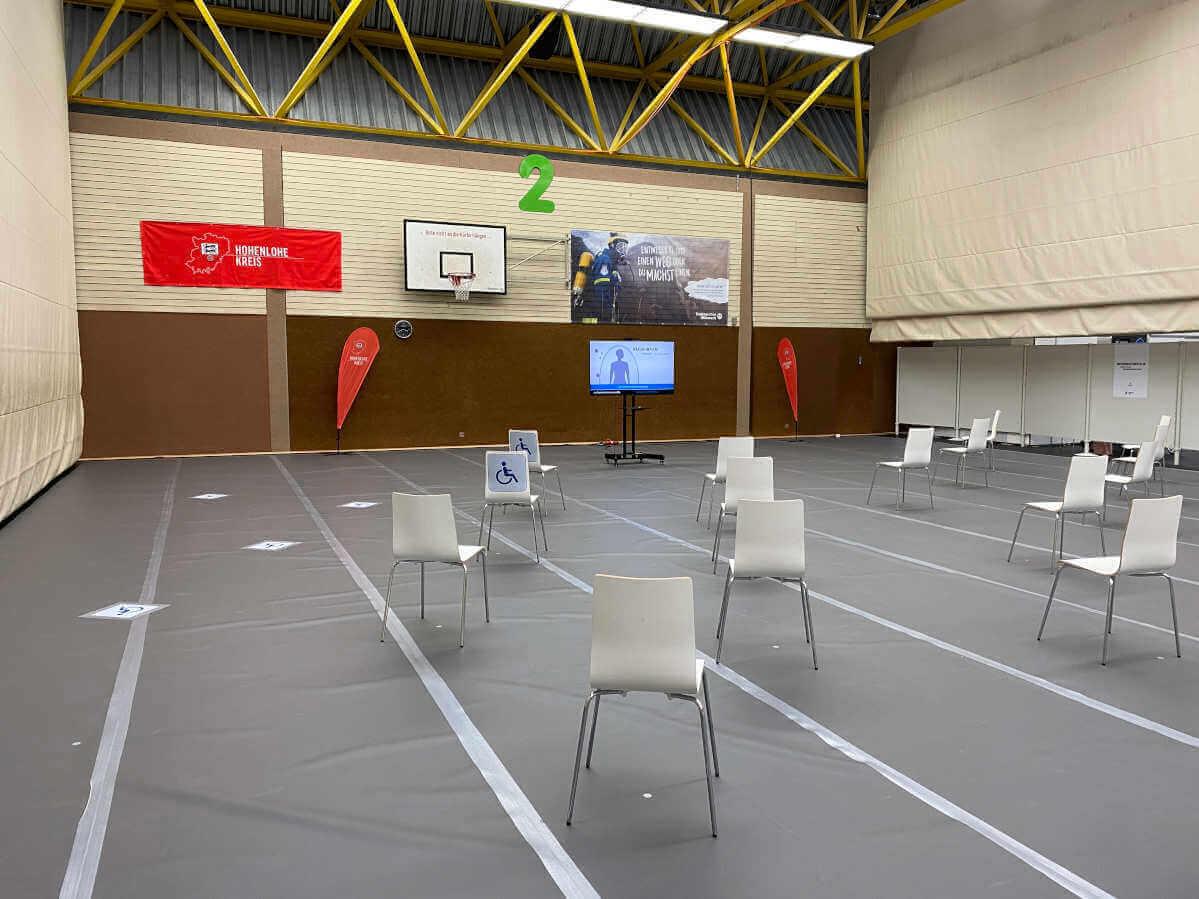 Die Wartepositionen im Impfzentrum Öhringen: Stühle sind mit Abstand zueinander in der Turnhalle aufgereiht.