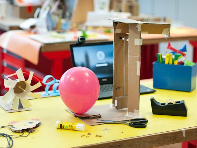 Das Bild zeigt einen Versuchstisch in einem Klassenzimmer, darauf liegen ein Luftballon und verschiedene Utensilien - ein Versuch vom Technoseum wird mit Online-Anleitung nachgebaut.