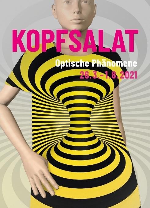 Das Plakat der Ausstellung Kopfsalat ist zu sehen: Eine gelb-schwarze Spirale als Oberkörper einer Puppe.