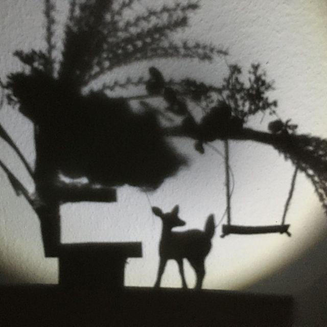 Ein Schattenspiel mit Baum, Reh und Schaukel ist zu sehen.