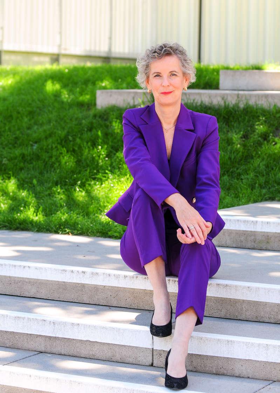 Das Bild zeigt die Expertin für Zukunftsforschung Universitätsprofessorin Marion Weissenberger-Eibl auf einer Treppe sitzend in einem violetten Anzug.