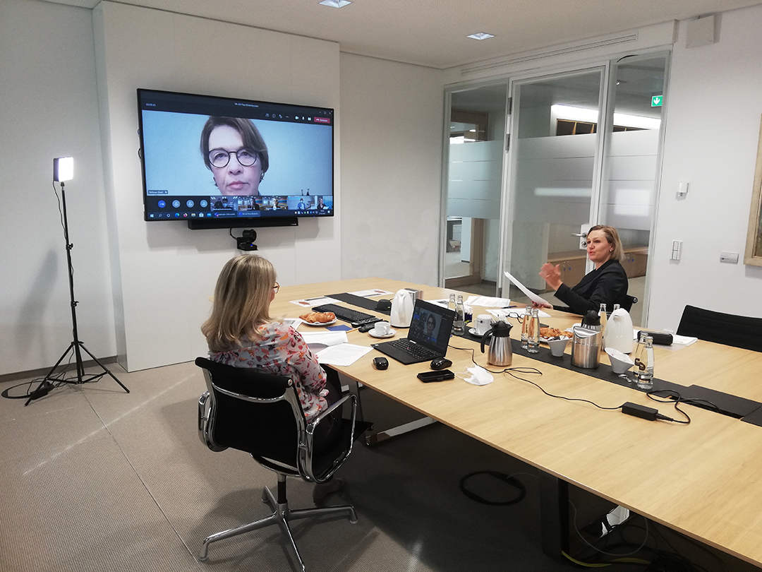 Das Bild zeigt zwei der Organisatorinnen der IHK vor einem Bildschrim, auf dem Elke Büdenbender zu sehen ist.