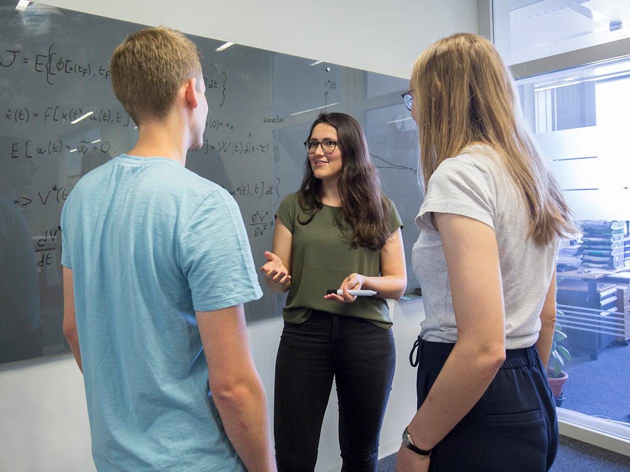Anne Koch erklärt Studenten eine Formel vor einem Whiteboard