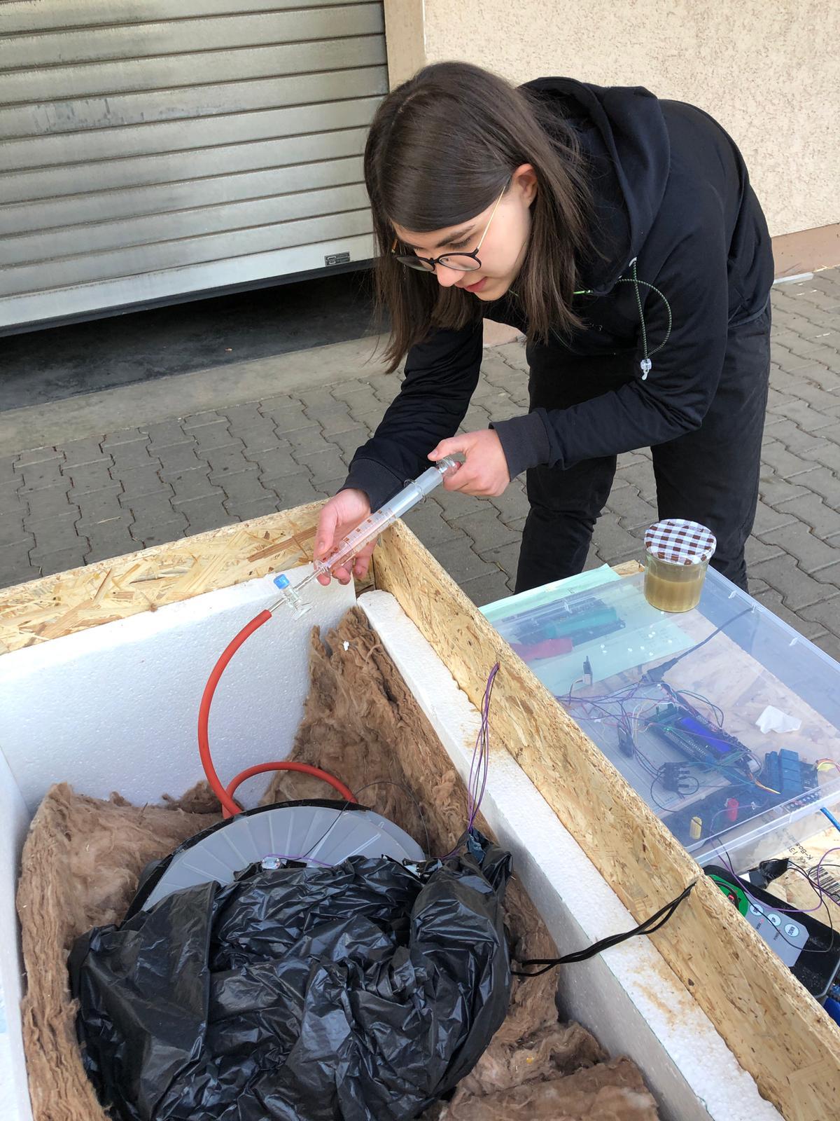 Das Bild zeigt die MINT-Schülerin Clara Springer beim Bau einer Biogasanlage.