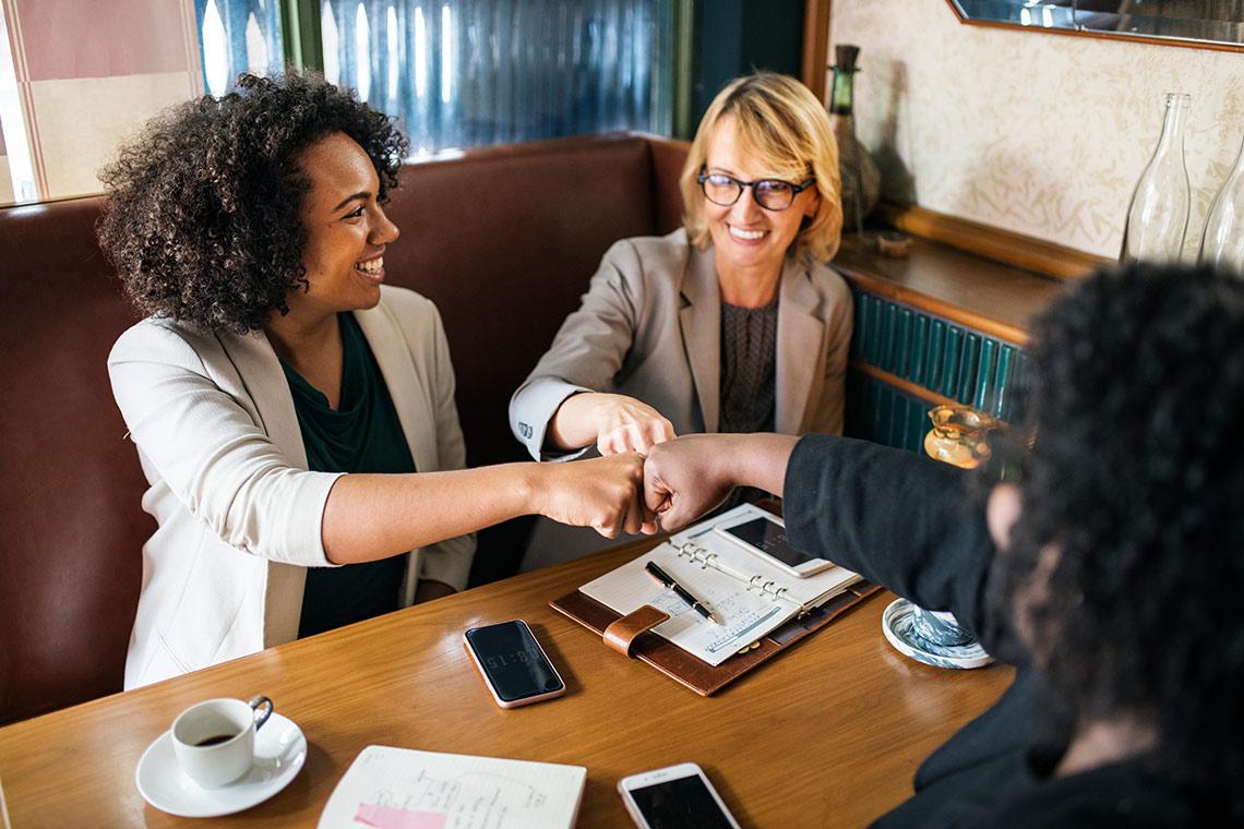 Drei Geschäftsfrauen geben sich gegenseitig einen Faustcheck.