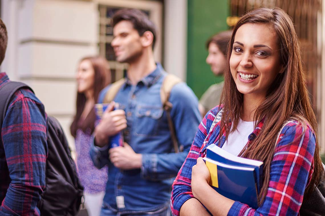 Eine junge Frau lächelt in die Kamera und hält ein Schulbuch in der Hand.