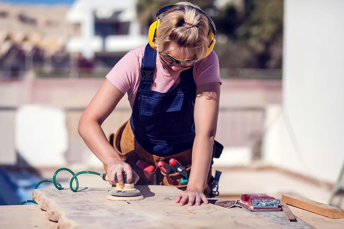Junge Handwerkerin beim Bearbeiten einer Holzplatte.