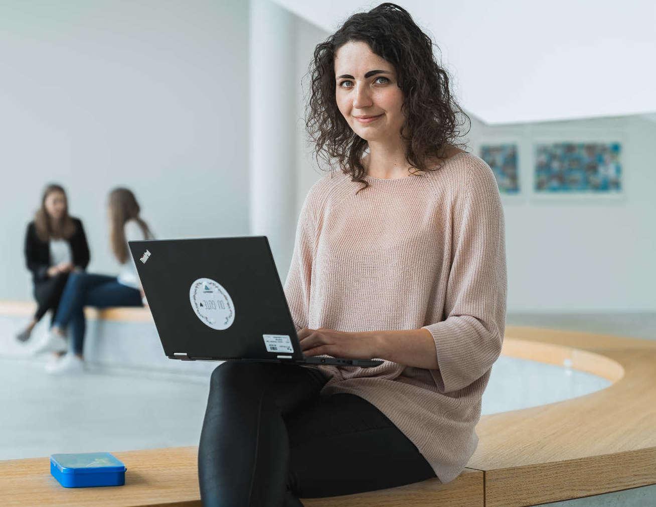 Patricia Haremski, Ingenieurin im Bereich Brennstoffzelle, sitzt mit Laptop auf dem Schoß auf einer Open Workspace-Fläche von Bosch in Renningen.